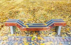 Banco di legno variopinto solo in parco in autunno fotografia stock