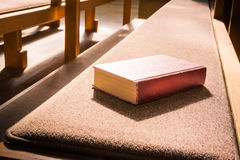 Banco di menzogne Woodd C del banco di chiesa della chiesa del vecchio della bibbia modello vuoto rosso del libro fotografia stock