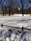 Banco di parco berried in neve in Central Park immagini stock