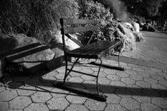 Banco di parco con le grandi pietre sul passaggio pedonale al parco in bianco e nero Immagine Stock Libera da Diritti