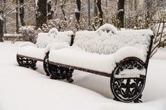 Banco di parco coperto di neve bianca fresca Fotografia Stock