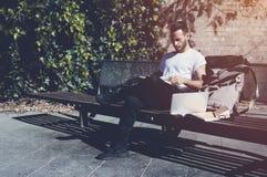 Banco di parco della città della maglietta bianca dell'uomo barbuto della foto e libro di lettura di seduta d'uso Studiando all'u Immagine Stock Libera da Diritti