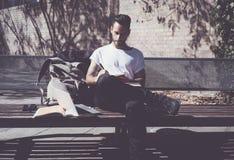 Banco di parco della città della maglietta bianca dell'uomo della foto e manuale di seduta d'uso di scrittura Studiando all'unive Immagine Stock