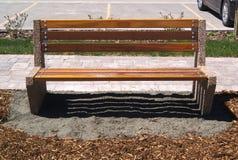 Banco di parco di legno che si siede sulla ghiaia e sul pacciame grigi Immagine Stock