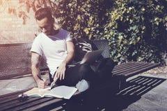 Banco di parco di seduta d'uso della città della maglietta bianca dello studente e scrivere il messaggio del manuale Studiando al Fotografie Stock Libere da Diritti