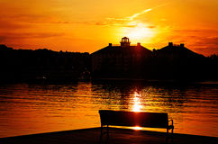 Banco di parco profilato dal lago al tramonto Fotografia Stock