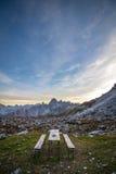 Banco di picnic nel paesaggio alpino sbalorditivo al tramonto La montagna Fotografia Stock Libera da Diritti