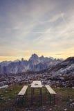 Banco di picnic nel paesaggio alpino sbalorditivo al tramonto La montagna Immagine Stock