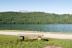 Banco di pietra nel lago Levico, Dolomiti, Italia immagine stock