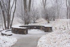 Banco di pietra in un parco all'inverno fotografia stock