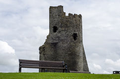 Banco di sosta vuoto con rovina del castello nella priorità bassa Immagini Stock Libere da Diritti