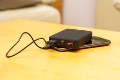 Banco do poder do bloco da bateria que carrega um telefone esperto móvel foto de stock royalty free