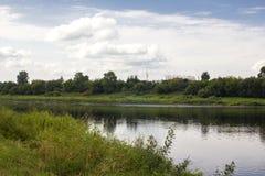 Banco do rio e do céu nebuloso imagens de stock