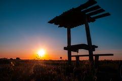 Banco ed albero di picnic profilati al tramonto immagine stock libera da diritti