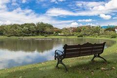 Banco en el parque cerca del pequeño lago Imagenes de archivo