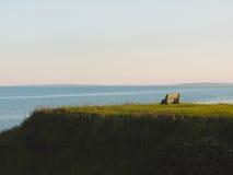 Banco en la colina de la hierba verde imagen de archivo libre de regalías