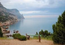 Banco en medio de rocas en el mar Fotografía de archivo libre de regalías