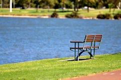Banco en parque cerca del agua imagen de archivo libre de regalías