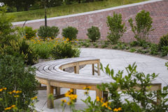 Banco en patio del ladrillo del jardín Fotos de archivo