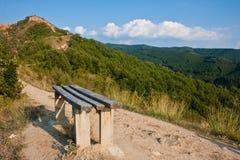 Banco en un camino de la montaña Imagenes de archivo