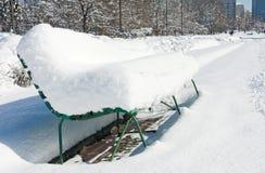 Banco en una ciudad cubierta por la nieve Imagenes de archivo