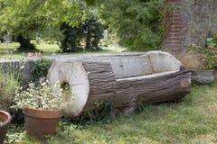 Banco fatto da un tronco di albero Fotografie Stock Libere da Diritti