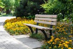Banco hermoso en el parque Cama de flor Fotografía de archivo libre de regalías