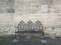 Banco isolato contro la vecchia parete di pietra immagine stock libera da diritti