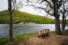 Banco a lo largo del lago hessian, en el parque de estado de la montaña del oso, Nueva York imagenes de archivo