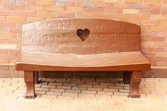 Banco marrone di legno con un cuore sulla parte posteriore vicino al muro di mattoni sulla via della città fotografie stock libere da diritti