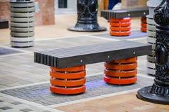 Banco moderno en un parque con los polos coloreados del metal Concepto de banco de la ciudad foto de archivo