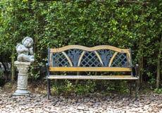 Banco no parque e em uma estátua Imagens de Stock Royalty Free