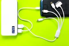 Banco ou bateria do poder conectado pelo fio ao smartphone fotos de stock