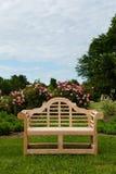 Banco ou cadeira do Teak no ajuste do jardim Fotografia de Stock Royalty Free