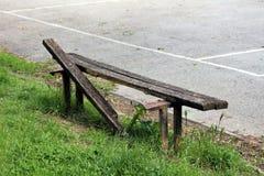 Banco público de madera roto montado en ayuda aherrumbrada del metal al lado del patio pavimentado rodeado con la hierba sin cort imagen de archivo