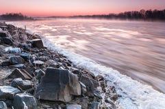 Banco pedregoso de un río de congelación cubierto en niebla durante oscuridad foto de archivo libre de regalías