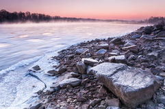 Banco pedregoso de un río de congelación cubierto en niebla durante oscuridad foto de archivo