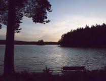 Banco pelo lago no por do sol bonito fotos de stock royalty free