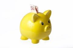 Banco piggy cerâmico amarelo com uma nota de banco Fotos de Stock Royalty Free