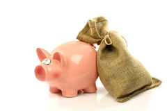 Banco piggy cor-de-rosa e um moneybag Fotografia de Stock Royalty Free
