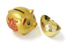 Banco Piggy dourado com lingote do ouro Imagem de Stock