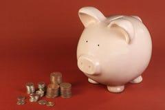 Banco Piggy e moedas Imagem de Stock Royalty Free
