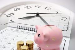 Banco Piggy e moedas no calendário foto de stock royalty free