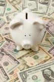 Banco Piggy em contas de dólar Fotografia de Stock Royalty Free