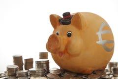 Banco Piggy em moedas Fotos de Stock Royalty Free
