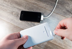 Banco portátil blanco del poder y teléfono móvil Fotos de archivo libres de regalías