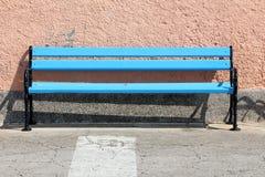 Banco pubblico di legno blu lungo con la struttura nera del ferro montata dal lato del marciapiede pavimentato davanti alla paret fotografia stock libera da diritti