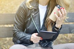 Banco que se sienta Autumn Park Reading de la mujer bastante joven un libro en el dispositivo de Digitaces fotos de archivo libres de regalías