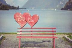 Banco rojo con el corazón cerca del lago Imagen de archivo
