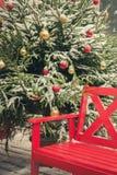Banco rojo decorativo tradicional para relajarse en una feria de la ciudad Luz de la noche Navidad imagen de archivo